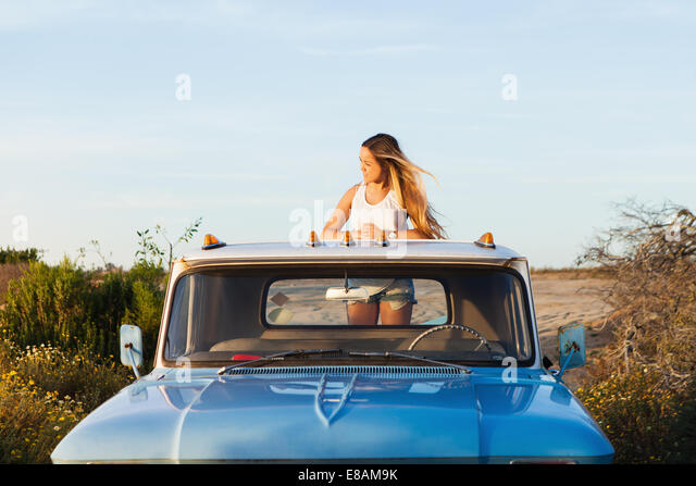 Young woman looking from the back pickup truck - Stock Image