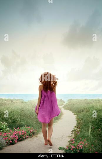Woman walking on flowery beach - Stock Image
