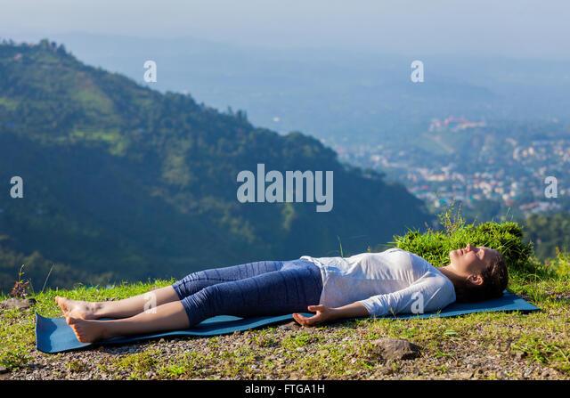 Woman relaxes in yoga asana Savasana outdoors - Stock Image