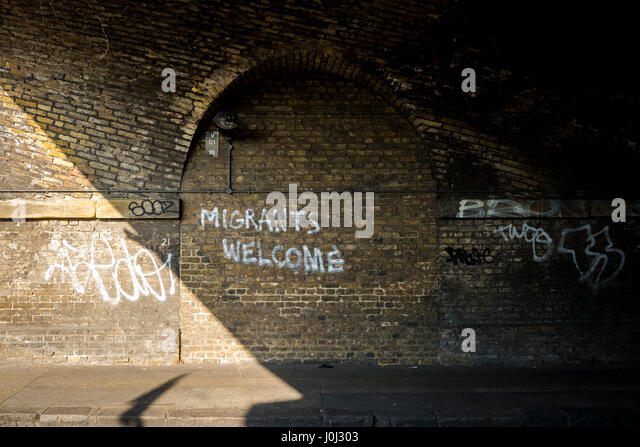 Graffiti in Londons Bethnal Green welcoming migrants. - Stock Image