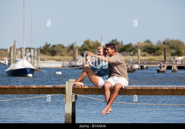 Couple sitting on a dock - Stock Image