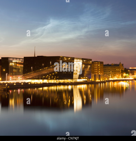 Lit buildings reflected in urban canal - Stock Image