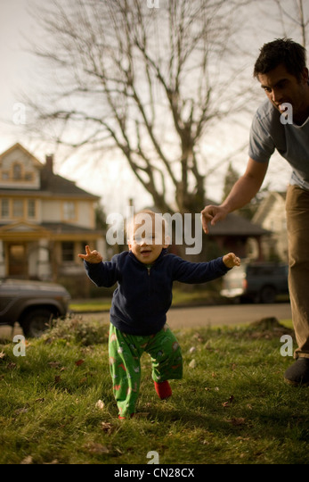 Father with son taking first steps - Stock Image
