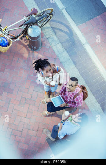 Friends using digital tablet on city street - Stock Image
