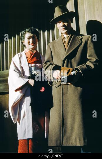 Two Western visitors to Japan pose for a photograph, the man wearing a trench coat and hat and holding a camera, - Stock Image