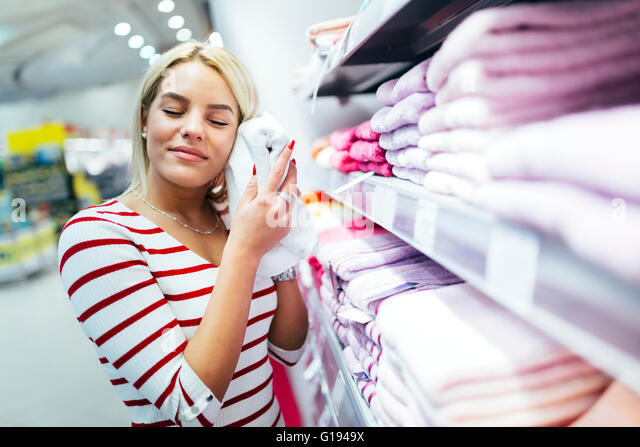Beautiful woman inspecting and buying towels in supermarket - Stock Image