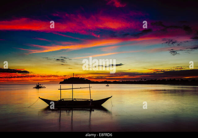 Philippines, Occidental Mindoro, Sablayan, Silhouette of boat at Sunset - Stock Image