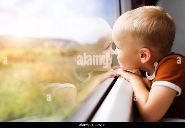 Little boy traveling in train looking outside the window. - Stock Image