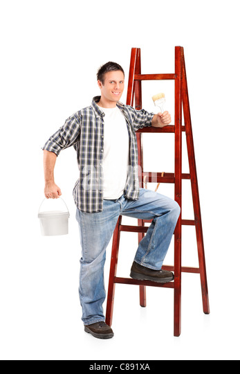 A male standing next to a wooden ladder and holding a paint brush and bucket - Stock Image