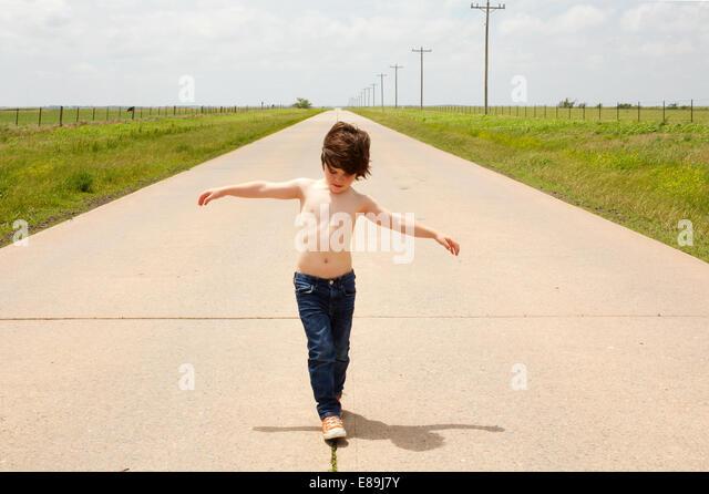 Boy walking along sidewalk - Stock-Bilder
