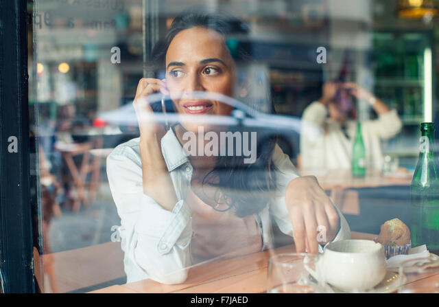 Woman talking on cell phone in coffee shop - Stock Image