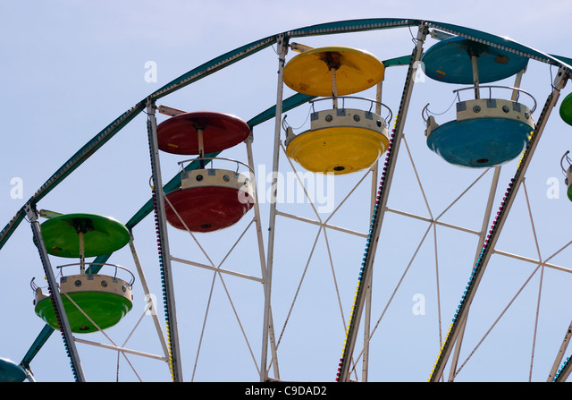 Colorful cars with canopies on a fairground ferris wheel ride. - Stock Image