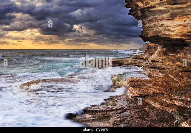 pacific ocean endless waves undermining sandstone rocks of Australian coast near Sydney during stormy sunrise - Stock Image