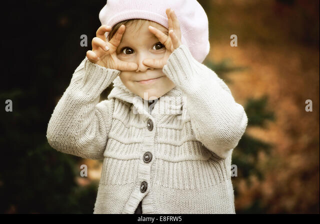 Child framing face with hands - Stock-Bilder