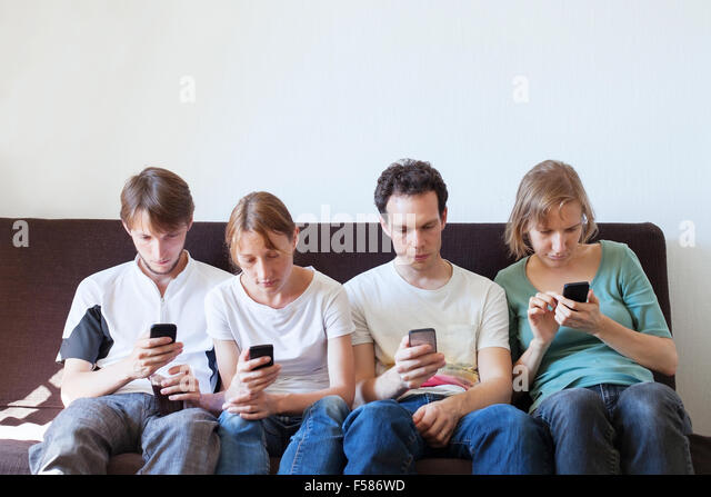 internet addiction, group of young people looking at their smart phones - Stock Image