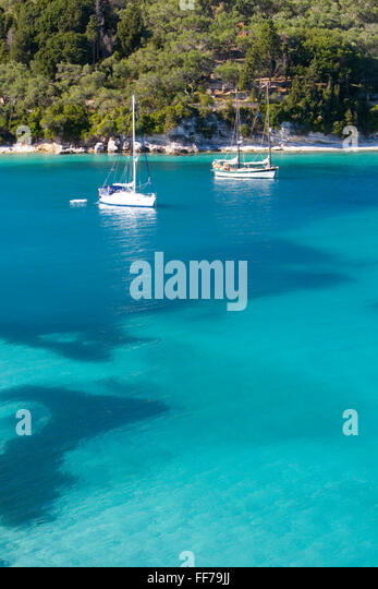 Lakka, Paxos, Ionian Islands, Greece. View from hillside over the clear turquoise waters of Lakka Bay, yachts at - Stock Image