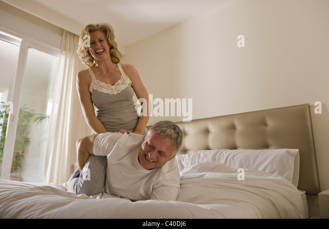 Mature couple wrestling on bed - Stock Image