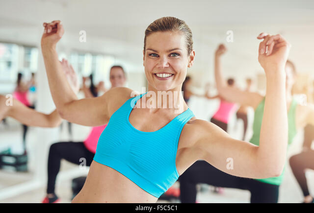Fit woman in a gym class, fitness, sport, training, gym and lifestyle concept - Stock Image