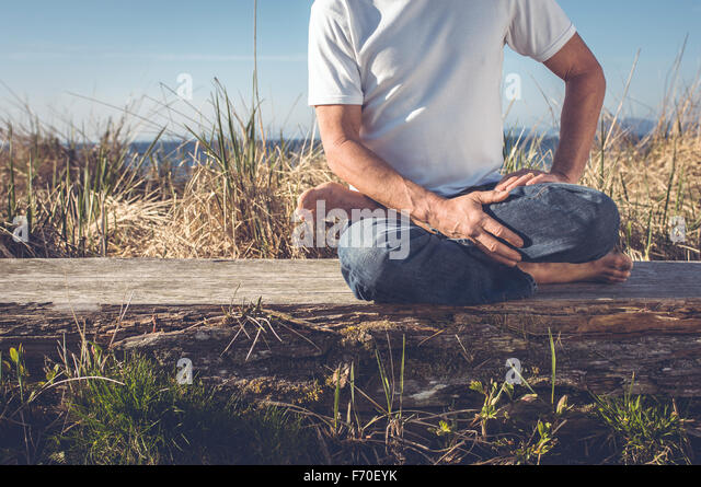 Older middle aged man, healthy and handsome practicing yoga at the beach in the sunshine. - Stock Image