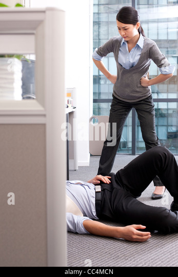 Businesswoman angry at her colleague lying on the floor - Stock Image