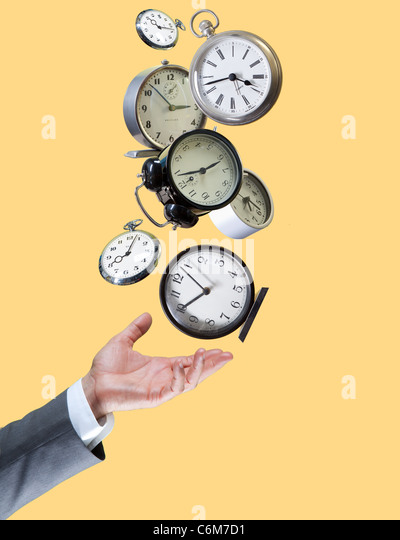 hand balances many clocks - Stock Image