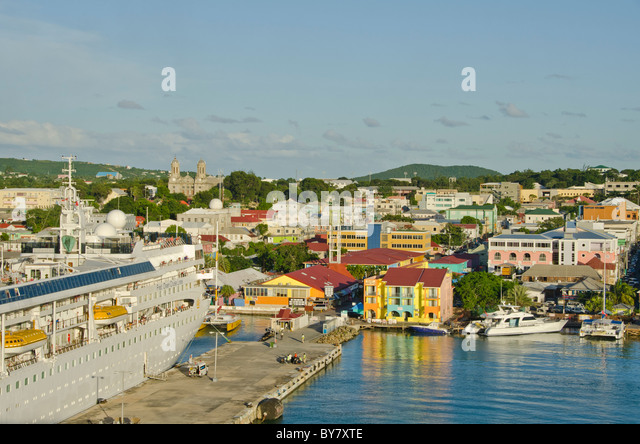 Antigua St. Johns cruise port dock with moored ship and cityscape in bright colors from Caribbean cruise ship - Stock Image