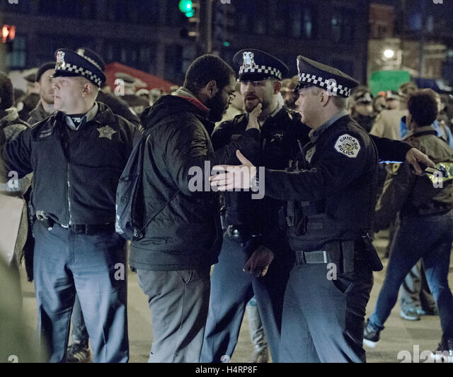 A black protester throws his hands up in the air saying 'Don't touch me' as Chicago Policemen attempt - Stock Image
