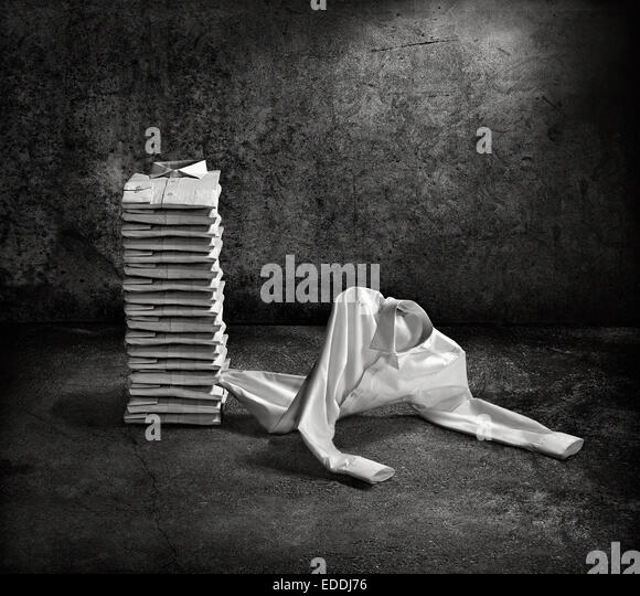 Stack of folded shirts and one escaping - Stock Image