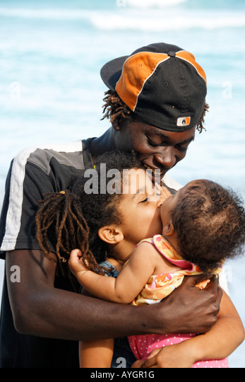 Jamaica Boston bay Jamaican father with kids kissing each other - Stock Image