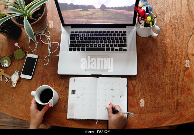 Person writing in diary with laptop on desk - Stock Image