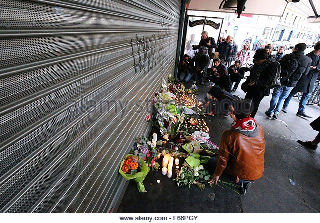 Paris, France. 14th November, 2015. People place flowers and candles outside the cafe 'La Belle Equipe' - Stock Image