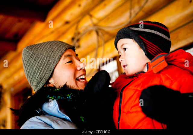 a woman is bundled up in warm clothes and stock cap / hat in a while holding her son in a log cabin. - Stock Image