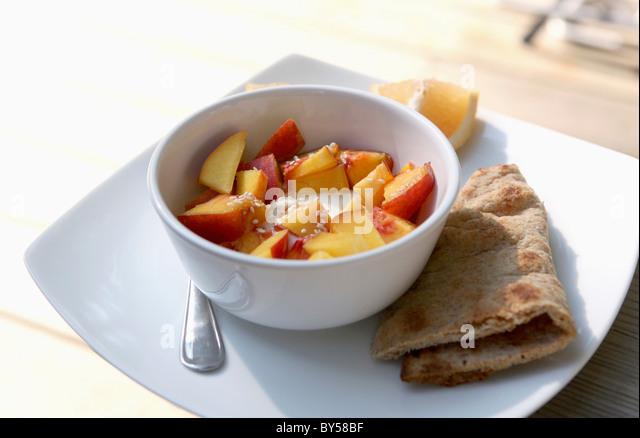 A bowl of yogurt with fresh nectarines - Stock Image