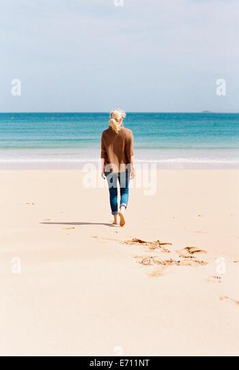 A woman walking barefoot on a beach, leaving footprints in the sand. - Stock-Bilder