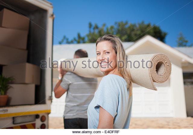Couple carrying carpet from moving van - Stock-Bilder