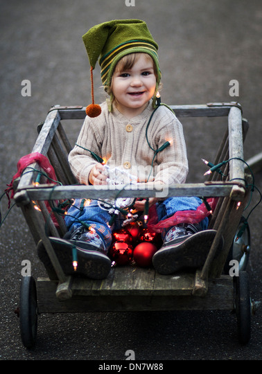 Little boy sitting with Christmas decoration in hand cart - Stock Image
