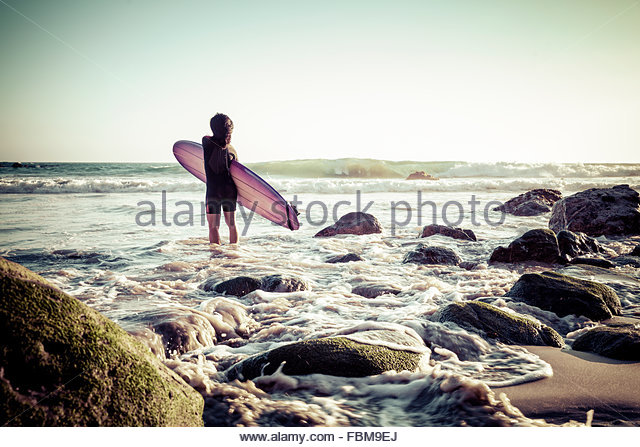 Woman standing in the surf with her surfboard, California, America, USA - Stock Image