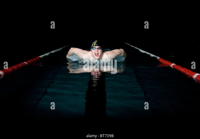Professional swimmer taking breath during butterfly swimming - Stock Image
