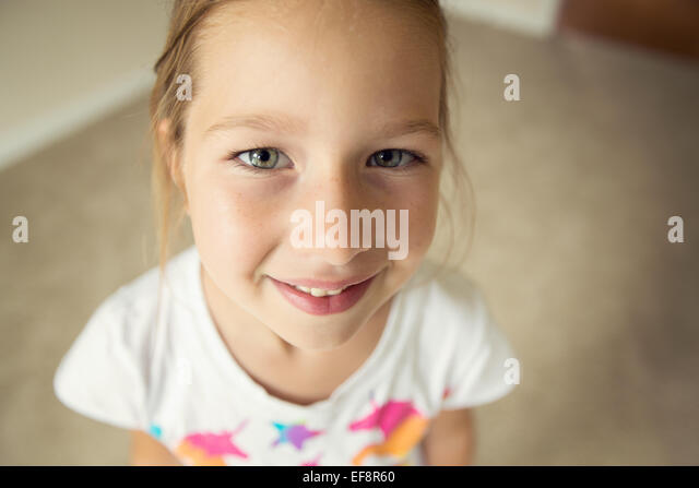 Portrait of smiling girl (6-7) looking up at camera - Stock Image