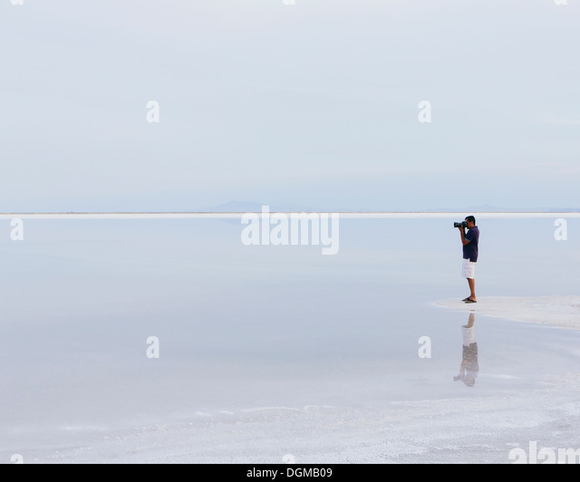 A man standing on the edge of the flooded Bonneville Salt Flats, taking a photograph at dusk. - Stock Image