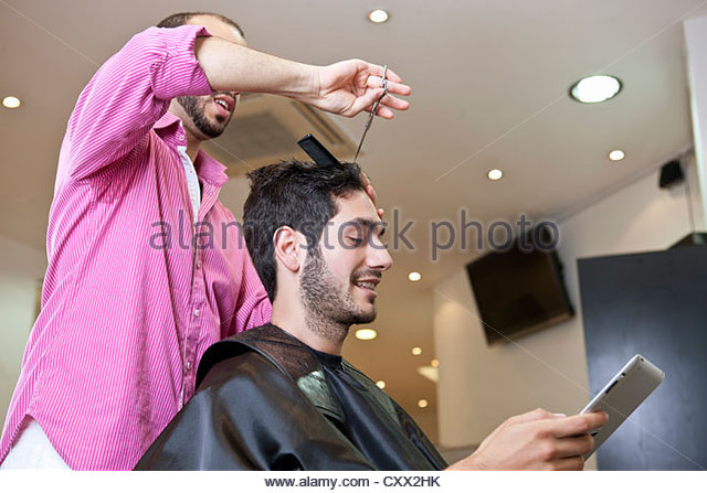 A male client looking at a digital tablet whilst having his hair cut - Stock Image