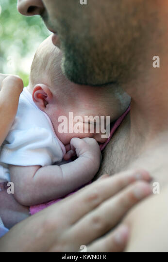 young man holding baby - Stock Image