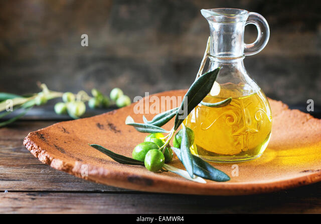 Bottle of olive oil with olive branch in handmade clay plate over wooden table. - Stock Image