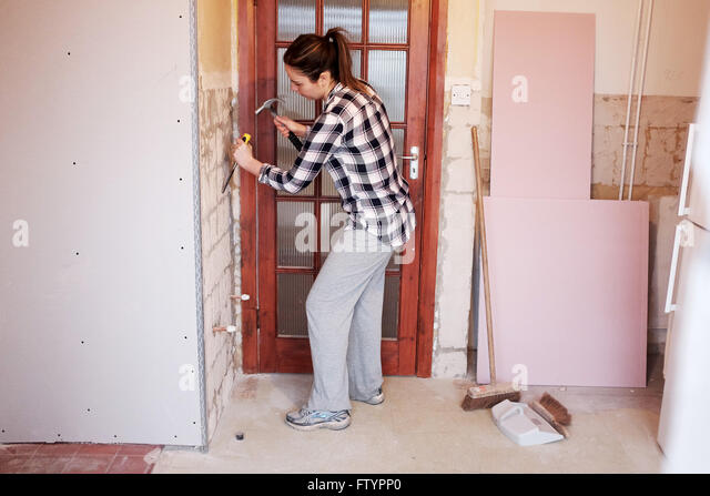 Young woman with hammer and chisel taking off wall tiles in kitchen in her 20s doing DIY at her bungalow home - Stock Image