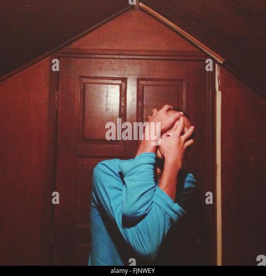 Man Covering Face With Hands Outside House - Stock Image