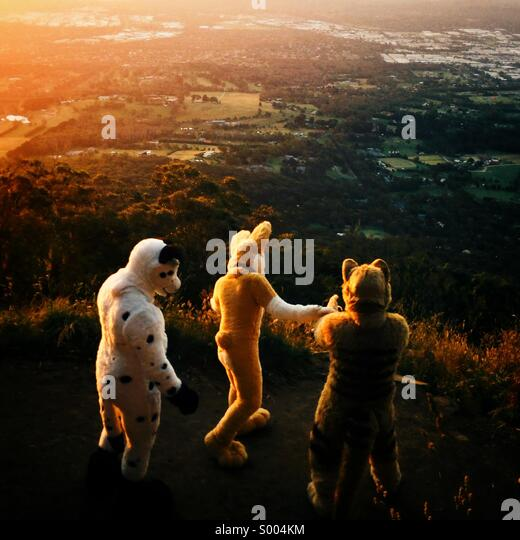 Quirky people in costumes at sunset - Stock Image