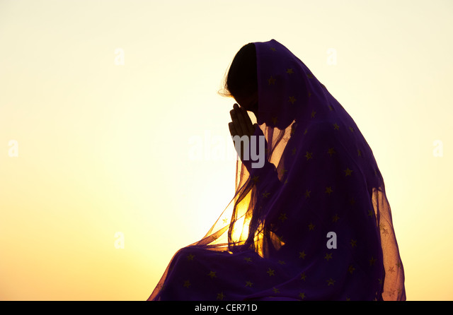 Indian teenage girl praying at sunset covered by a star veil. Silhouette. India - Stock Image