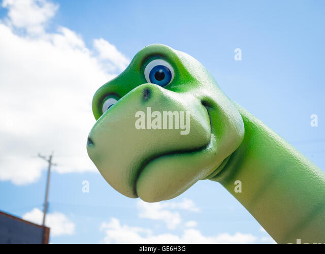 A friendly green dinosaur statue in the town of Drumheller, Alberta, Canada. - Stock Image