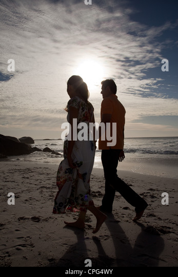 Couple holding hands and walking on beach. - Stock-Bilder