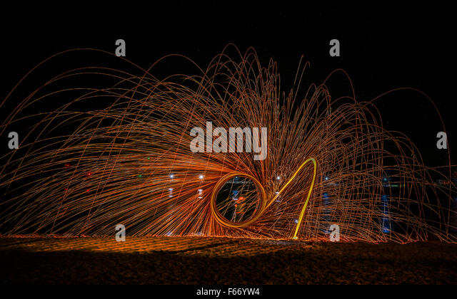 A pyrotechnic display painting with light on a beach during The Whitby Goth Weekend. - Stock Image